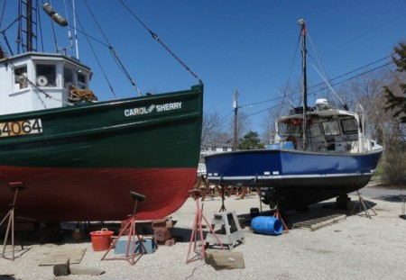 F/V All In (smaller blue boat) at a Wellfleet boatyard, by David W. Dunlap (2014).
